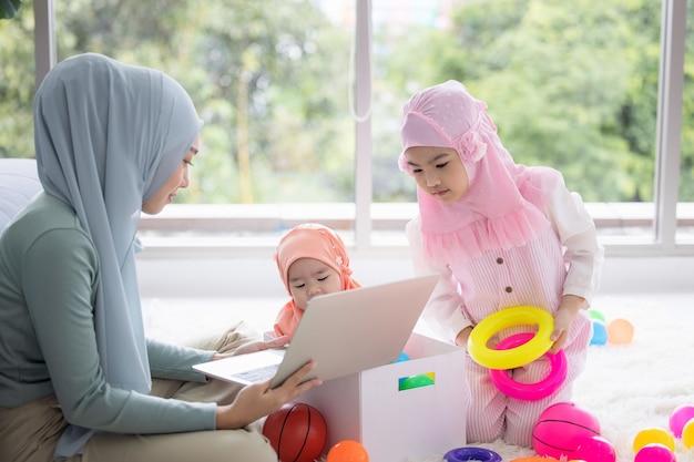 Мусульманская мать, работающая с ноутбуком и милый маленький ребенок, играя в игрушки в гостиной дома.