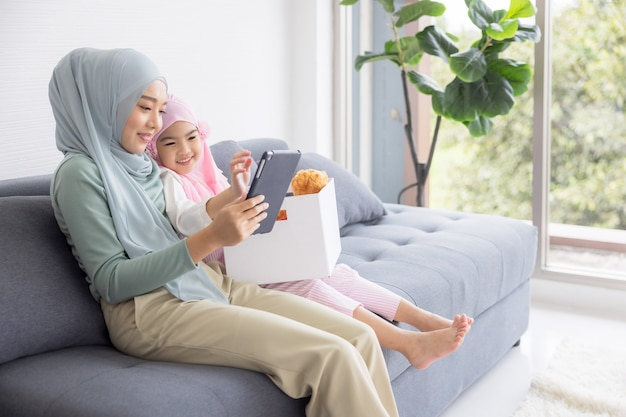ラップトップで作業しているイスラム教徒の母親と自宅のリビングルームでおもちゃを遊んでいるかわいい赤ちゃん。