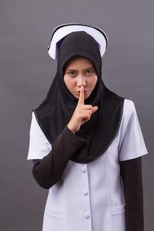 Muslim nurse hushing, asking for silence