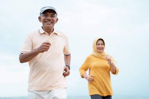 Muslim old couple workout and running at the beach
