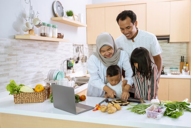 Muslim parent and kids enjoy cooking iftar dinner together during ramadan fasting at home