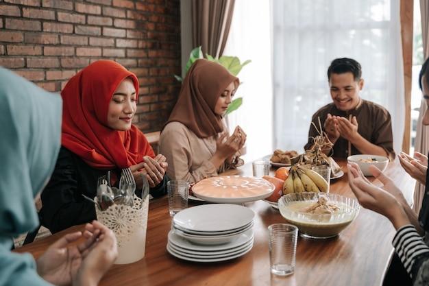 食事をする前に祈るイスラム教徒の人々