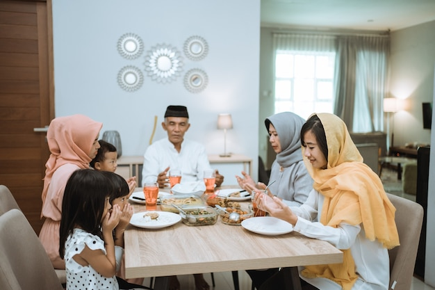 Muslim people praying during iftar dinner together with family in the kitchen at home