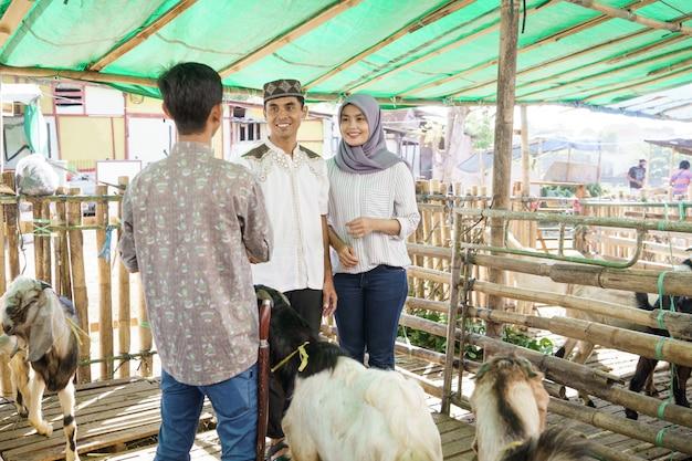 イスラム教徒の人々は、山羊を購入した後、農民と握手します。 idul adha犠牲の祭典