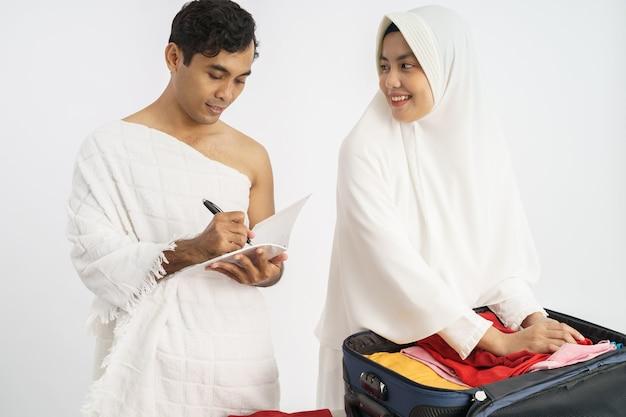 Жена и муж паломников-мусульман готовят предметы для хаджа в каабу