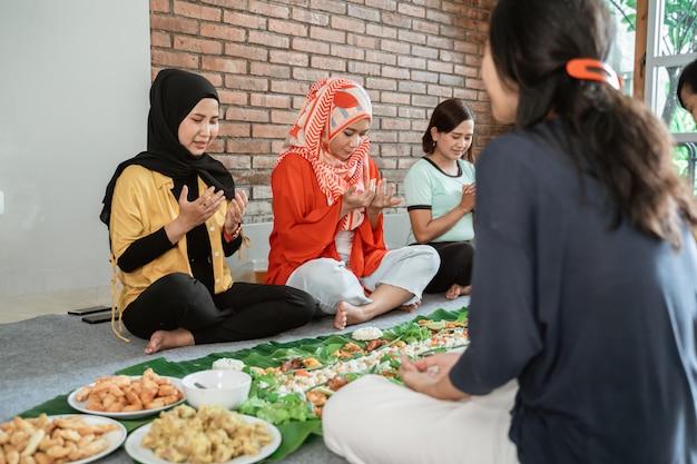 食べる前に祈るイスラム教徒