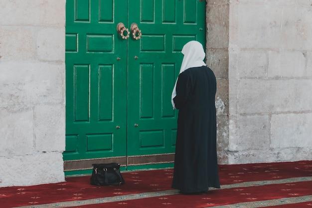 긴 드레스를 입고 머리를 덮은 이슬람 종교 여성이 모스크의 거대한 녹색 문에 서서 기도하고 있습니다. 예루살렘에 있는 바위의 돔 입구 근처에 서 있는 여성의 뒷모습.