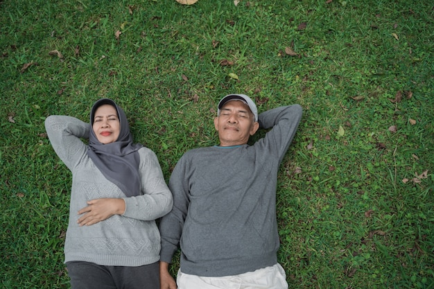이슬람 수석 남자와여자가 잔디에 누워