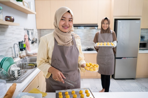 Muslim small business owner making homemade nastar snack to sell. beautiful asian woman with partner cooking and holding tablet pc