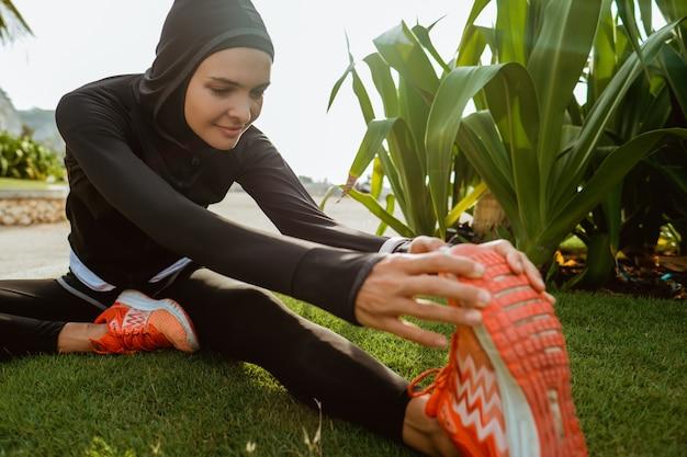 Мусульманская спортивная женщина вытянула ногу