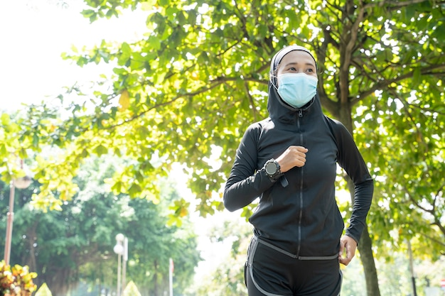 Мусульманская спортивная женщина в маске работает на открытом воздухе в парке