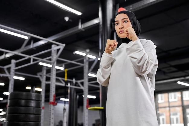 무슬림 운동가는 전투기 포즈에 서서 공격하려고하며, 젊은 여성은 흰색 히잡을 입고 피트니스 센터에서 권투에 종사하고 있습니다. 스포츠, 운동 및 피트니스 개념
