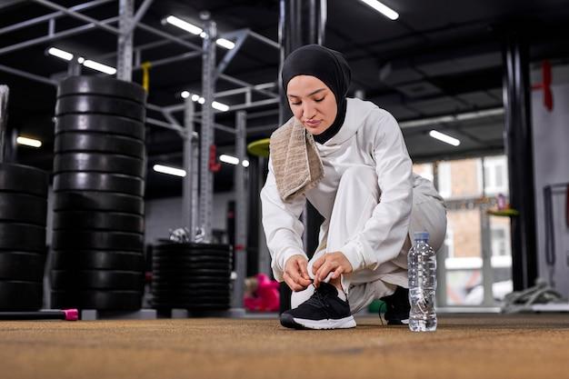 イスラム教徒のスポーツウーマンがスニーカーに靴ひもを結び、ジムでのトレーニングの準備をしている、白いスポーツヒジャーブを着用