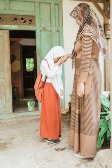 イスラム教徒の学生は朝学校に行く前に彼女の母親の手を振ってキスします