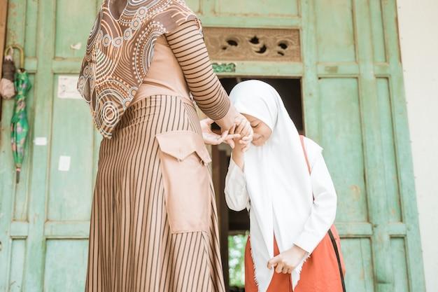 イスラム教徒の学生は、朝学校に行く前に母親の手を振ってキスします
