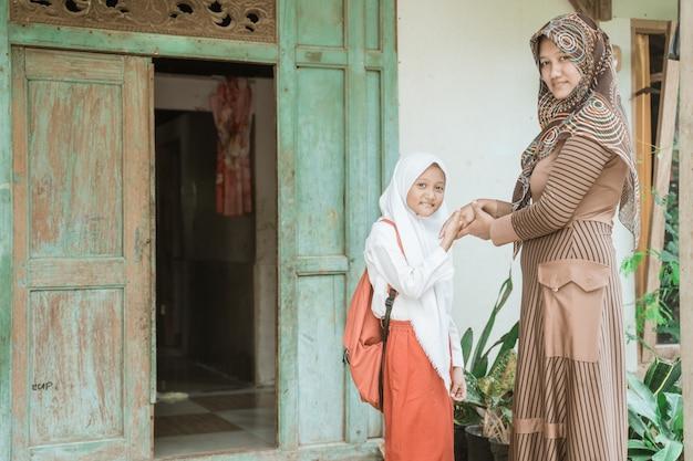 イスラム教徒の学生は朝学校に行く前に母親の手を振る