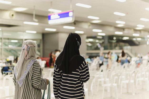 친구와 함께 건물에서 걷는 이슬람 학생
