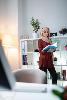 イスラム教徒の先生。生徒のためのレッスンを準備するスカーフを身に着けているスリムで魅力的なイスラム教徒の教師