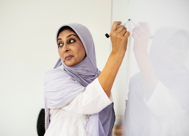 Muslim teacher writing on a white board