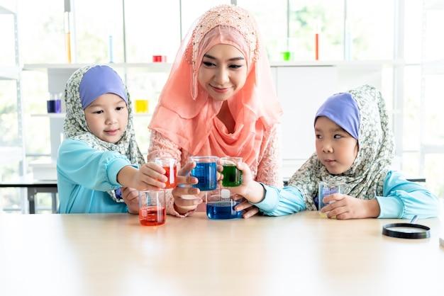 イスラムの服を着たイスラム教徒の教師がイスラム教徒の子供たちに科学実験について教えています