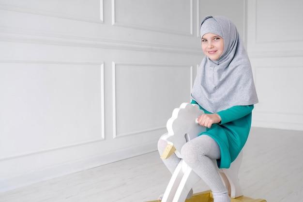 히잡과 드레스를 입은 이슬람 십대 소녀가 그녀의 방에서 장난감 말 흔들의자를 타고 놀고 있습니다.