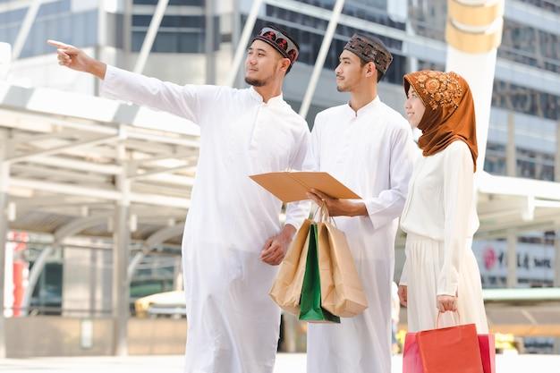 都市で買い物をするイスラム教徒の十代の読書、コンセプト教育とショッピング