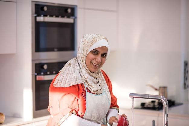 부엌에서 청소하는 이슬람 전통 여자