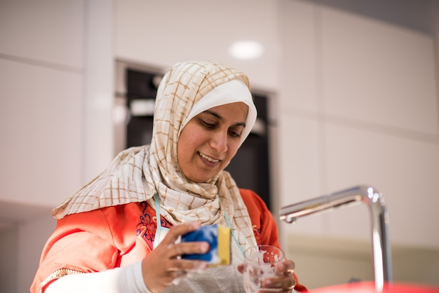 Muslim traditional woman cleaning in kitchen
