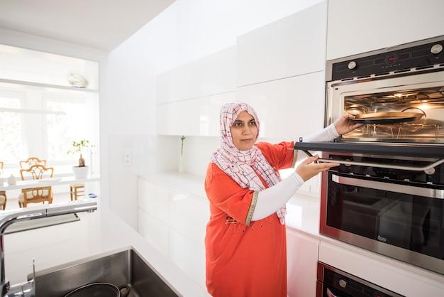 Muslim traditional woman using stove