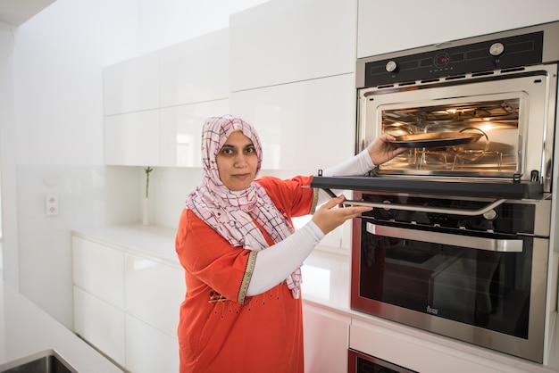 Muslim traditional woman using stove Premium Photo