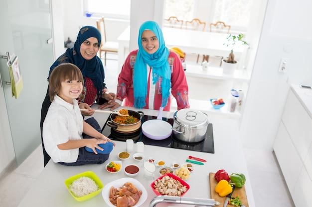 현대 흰색 부엌에서 작은 아들과 함께 이슬람 전통 여자
