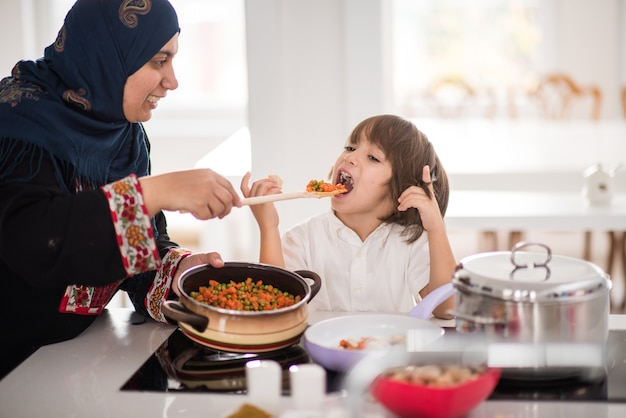 Muslim traditional woman with nice kid in house