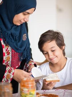 부엌에서 아들과 함께 이슬람 전통 여자 프리미엄 사진