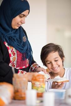 부엌에서 아들과 함께 이슬람 전통 여자