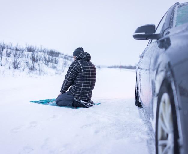 冬の山で祈るイスラム教徒の旅行者