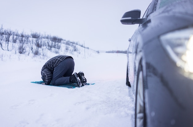 Muslim traveler praying in winter mountain