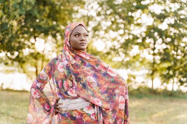 무슬림 여성 아프리카 민족 weared 전통적인 다채로운 히잡은 녹색 초원에 오른쪽으로 보인다