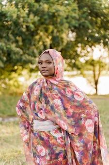 무슬림 여성 아프리카 민족은 녹색 초원에 전통적인 다채로운 히잡을 weared