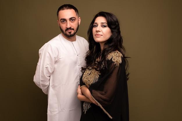 무슬림 여자와 남자. 젊은 아랍 소녀와 전통 복장에있는 남자의 초상화를 닫습니다.