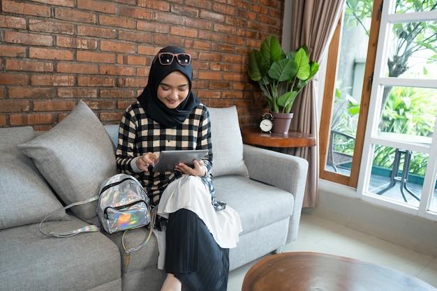 Мусульманская женщина дома используя таблетку