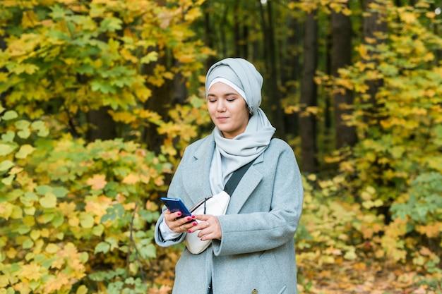 Мусульманка в парке с помощью смартфона подключила беспроводное онлайн-пространство для рекламы
