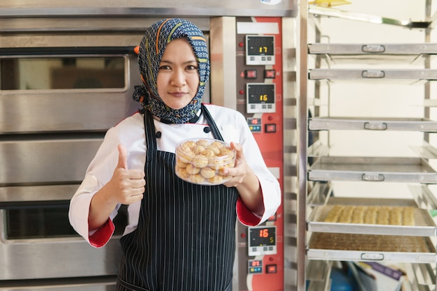 Muslim woman baker standing with her bakery