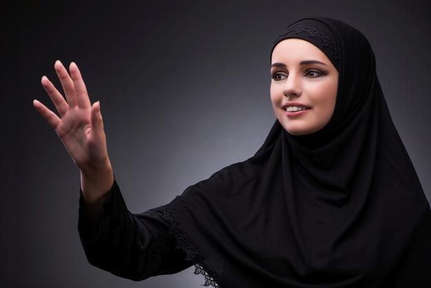 Muslim woman in black dress against dark background