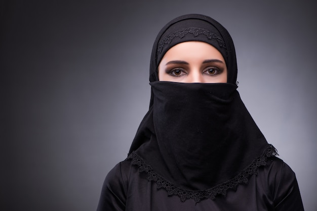 Muslim woman in black dress against dark background