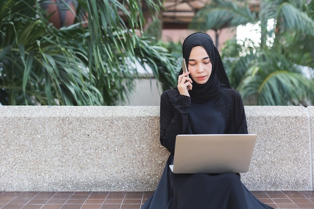 Muslim woman in black hijab talking telephone and working with laptop outdoor office.