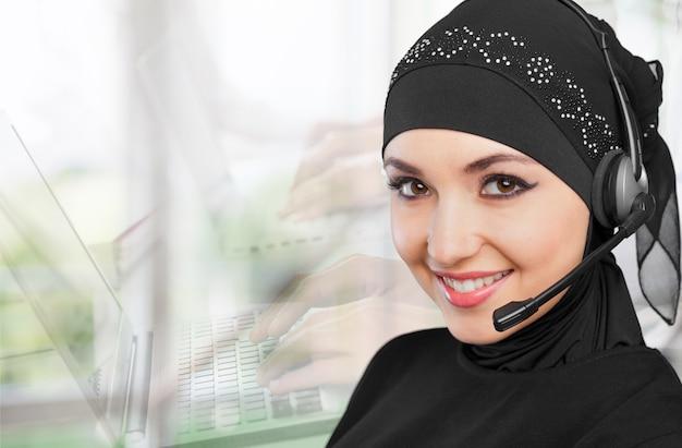 ヘッドセットを持つイスラム教徒の女性のコールセンターのオペレーター