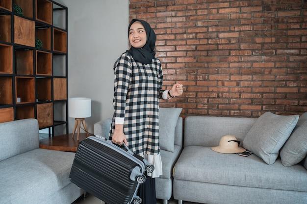スーツケースを運ぶイスラム教徒の女性