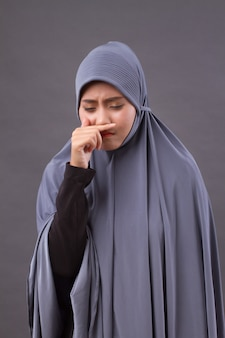Muslim woman catching a cold, runny nose