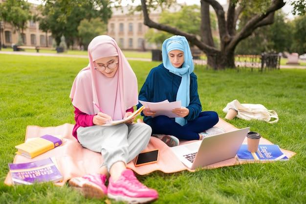 무슬림 여성. 친구와 함께 밖에 앉아 hijab를 입고 어두운 눈을 가진 이슬람 여자의 닫습니다