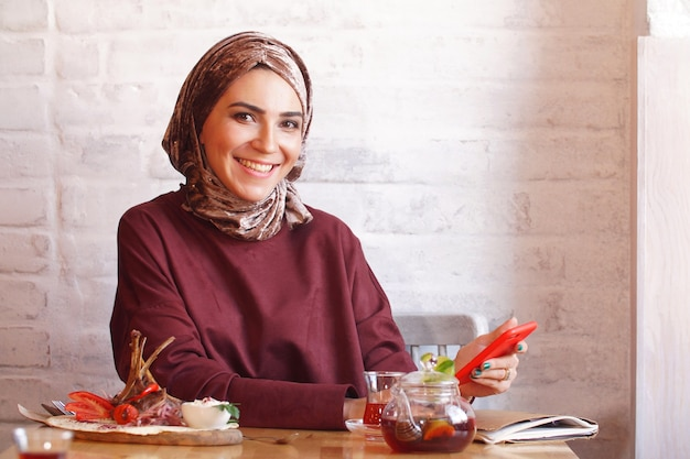 Muslim woman conducts correspondence on the phone sitting in a cafe